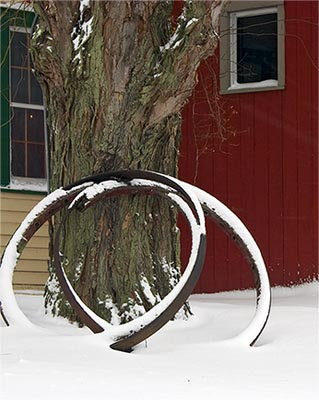 Two old wagon wheel hoops draped in the recent snow.